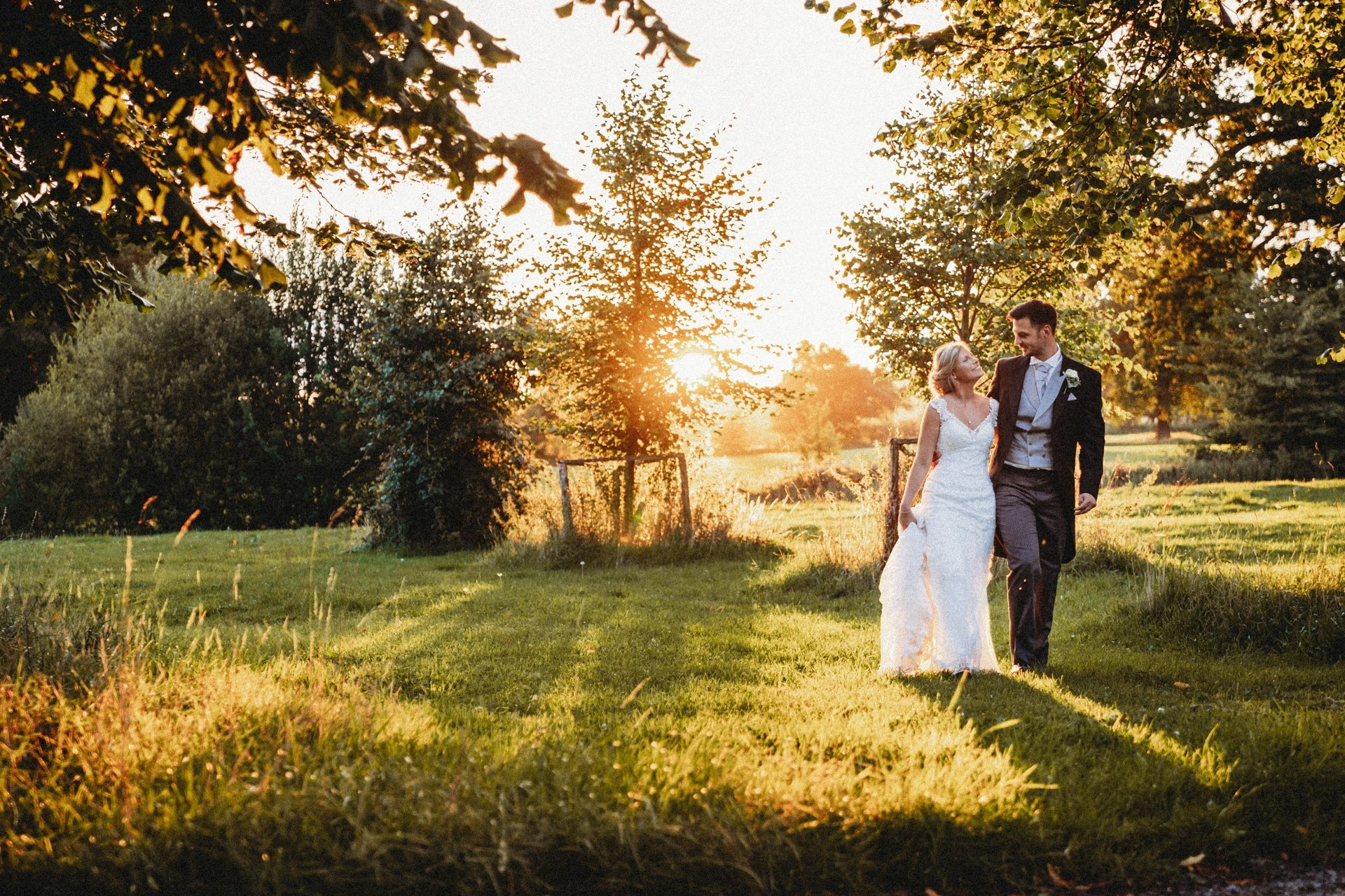 Loseley Park Wedding Photographer - couple walking through a golden sunset